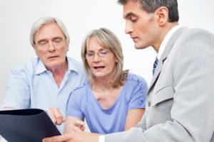 Senioren lassen sich im Wohnzimmer von einem Experten beraten